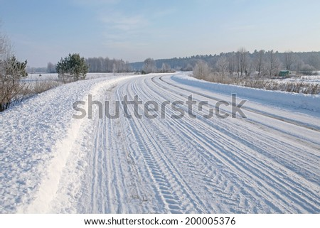 winter landscape of snowy road and woods on the horizon on a bright frosty day low angle view - stock photo