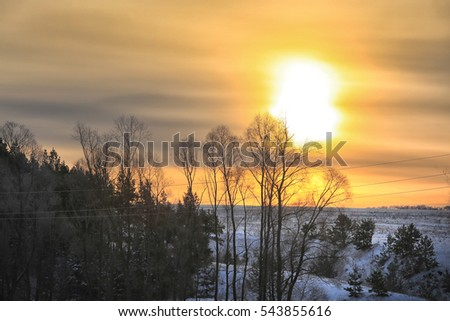 winter landscape of sunrise over the snow-covered field and trees