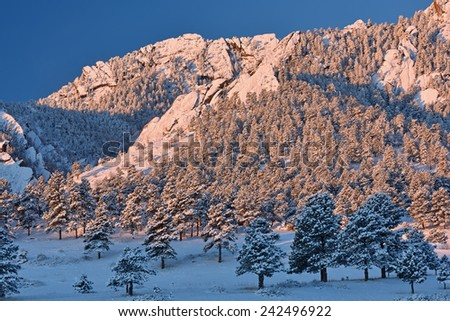 Winter landscape of the Flatirons flocked with snow at sunrise, Rocky Mountains, Boulder, Colorado, USA   - stock photo