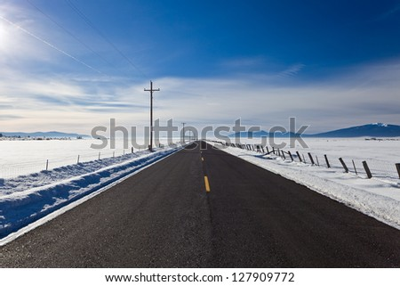 Winter landscape on a frosty day with a paved road.