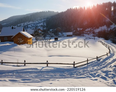 Winter landscape. Photographed at sunset in the mountain village. A lot of snow. Wooden houses, near the pine forest and the trees. See the beautiful texture of the snow. - stock photo
