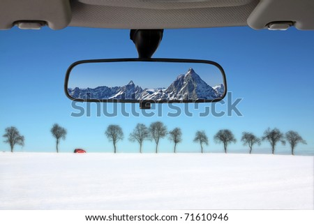 Winter landscape reflected in the car rear mirror