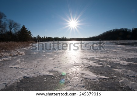 Winter landscape: Sun as a star burst shining on frozen lake on a very cold day - stock photo