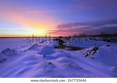winter landscape sunset on the ice of the river and the city on the horizon - stock photo