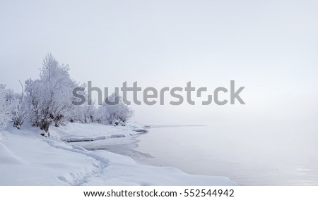 Winter landscape. Trees and bushes with hoarfrost. The water in the river floating mist. cold season. a white crystalline deposit of frozen water vapor formed in clear still weather, Altai, Russia
