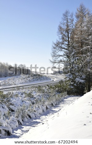 Winter landscape with a blue sky and lot of snow and also a motorway with one car - stock photo