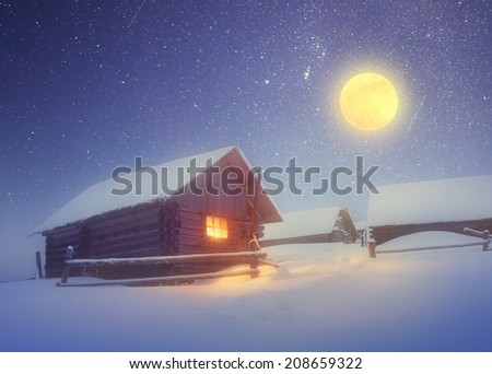 Winter landscape with a starry sky and the full moon. The light in the cabin in the mountains. Soft effect. Color toning - stock photo