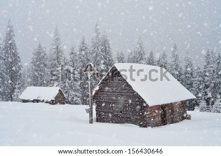 Winter landscape with a wooden hut in the mountains and the Orthodox cross. Ukraine, Carpathian Mountains - stock photo