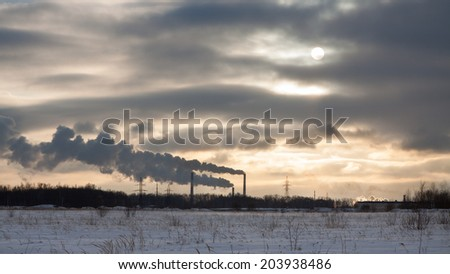 Winter landscape with factory chimneys and clouds against the sun - stock photo