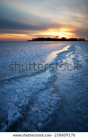 Winter landscape with frozen lake and sunset sky. Composition of nature.  - stock photo