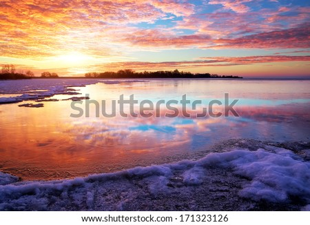 Winter landscape with lake and sunset fiery sky. Composition of nature.  - stock photo