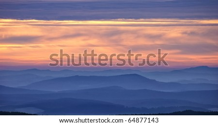 winter landscape with misty layered hills at sunrise - stock photo