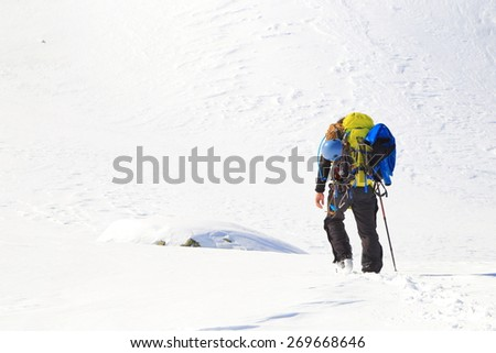 Winter landscape with mountaineer loaded with a heavy backpack on snowy slope - stock photo