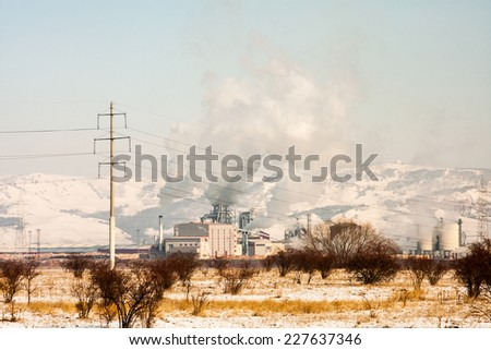 Winter landscape with refinery and smoky industrial background
