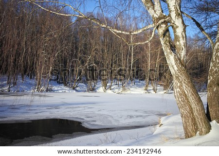 Winter landscape with river and blue sky in a sunny day.  - stock photo