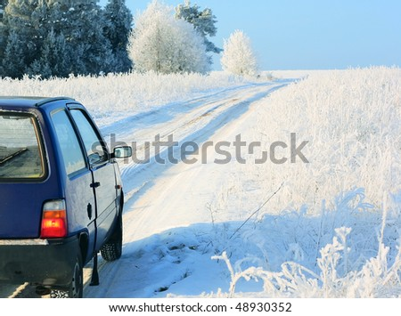 Winter landscape with road and blue car - stock photo