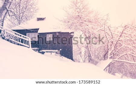 Winter landscape with snow covered trees on hill and an old house - Transylvania - stock photo