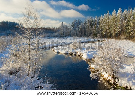 Winter landscape with the river, the blue sky and clouds - stock photo