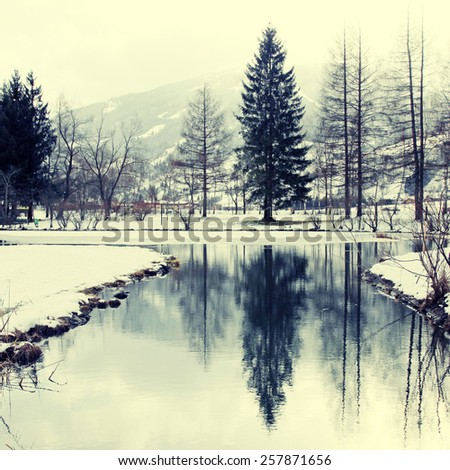 Winter landscape with trees and pond reflection in Alps mountains, Austria. Square toned image, instagram effect - stock photo
