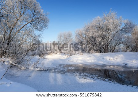 winter landscape with trees in frost near the frozen stream, Russia