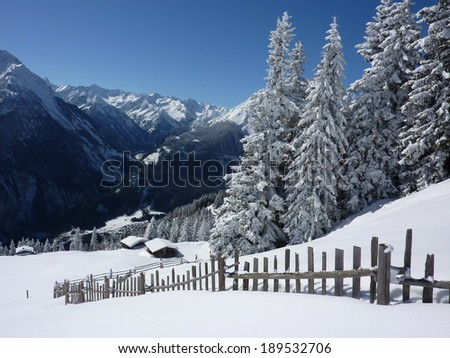 Winter landscape with wooden fence and ski chalets - stock photo