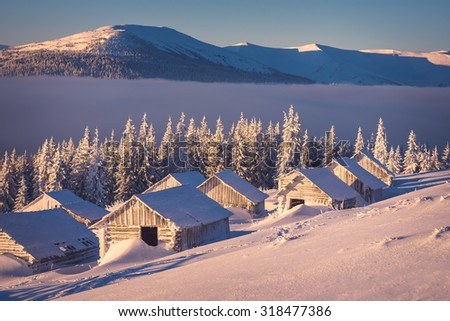 Winter landscape with wooden houses in the mountains. Sunny morning. The village of shepherds - stock photo