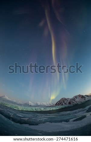 Winter lanscape of the Arctic - northern lights over the glacier - stock photo