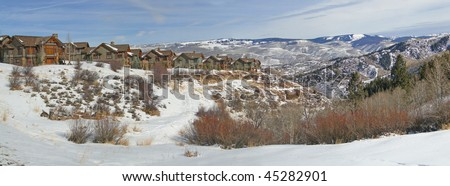 Winter, large houses overlook snowy field   above the Vail Valley, Colorado. - stock photo