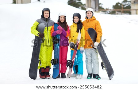 winter, leisure, extreme sport, friendship and people concept - happy friends in helmets with snowboards - stock photo