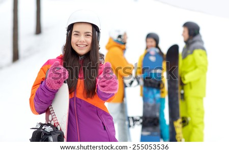 winter, leisure, extreme sport, friendship and people concept - happy young woman in helmet with snowboard and group of friends showing thumbs up - stock photo