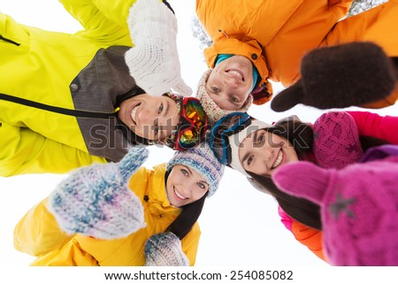 winter, leisure, friendship and people concept - happy friends standing in circle outdoors, showing thumbs up and and looking down - stock photo