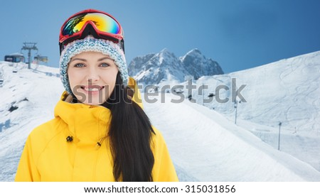 winter, leisure, sport and people concept - happy young woman in ski goggles over snow and mountain background - stock photo