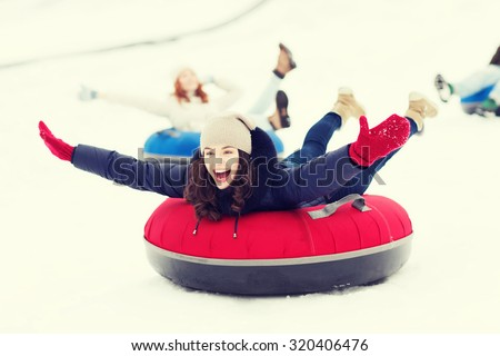 winter, leisure, sport, friendship and people concept - group of happy friends sliding down on snow tubes - stock photo