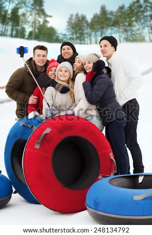 winter, leisure, sport, friendship and people concept - group of smiling friends with snow tubes taking picture by smartphone selfie stick outdoors - stock photo