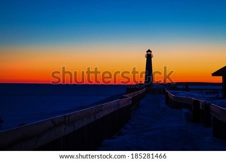 Winter Lighthouse Sunrise. The Wawatam Lighthouse in at dawn. St. Ignace, Michigan. - stock photo