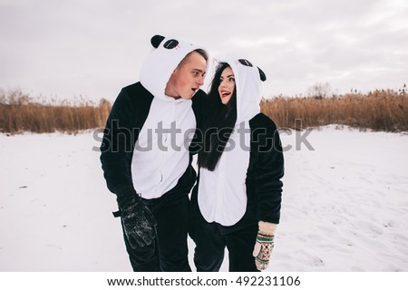 winter love story, a beautiful young couple in suits pandas