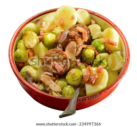 Winter meal. Seasonal fare of potatoes, Brussels sprouts and sausage slices garnished with onion and bacon in rustic enamel serving dish. Isolated. - stock photo
