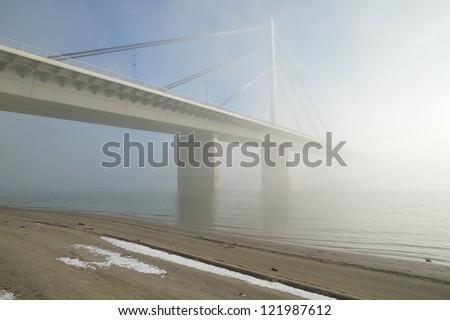 Winter morning by Danube river with bridge in fog - stock photo