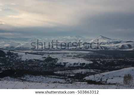 Winter mountain hill slope field with snow on the background of village town in dark cloud gloom dramatic grim dusk evening weather Altai Mountains Siberia Russia