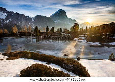 Winter mountain landscape with frozen lake in the front and dramatic sky of evening sun in the background, sunrays protruding trees. Wilderness, raw nature concept and background. Limides, Dolomites. - stock photo