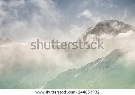 Winter mountain peaks in the clouds. Caucasus, Russian Federation. Beautiful winter landscape. Creative toning effect - stock photo