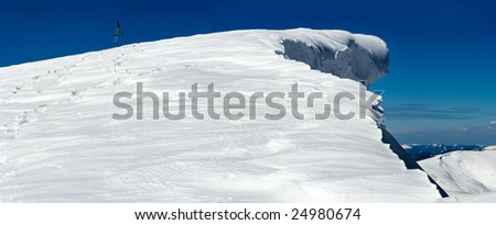 Winter mountain top with fairy overhang snow cap and human footprint on snowy mountainside follow up to photographic tripod (five shots stitch image)