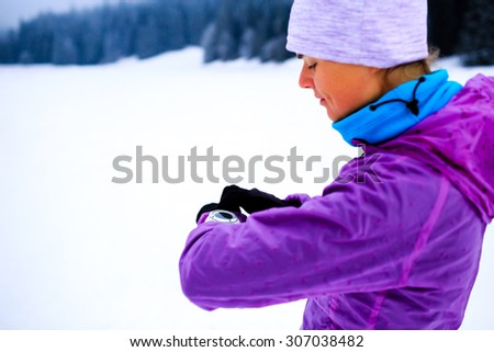 Winter mountain trail running woman checking looking at sportwatch smart watch, cross country runner checking performance, GPS position or heart rate pulse. Sport smartwatch and fitness equipment - stock photo