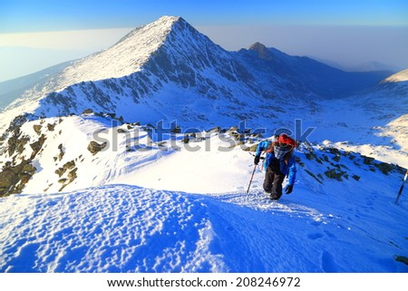 Winter mountaineer ascends a snow covered slope in sunny evening - stock photo