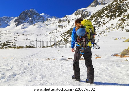 Winter mountaineer carries a backpack on snow covered mountain - stock photo