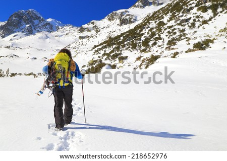 Winter mountaineer carries climbing gear on snowy trail