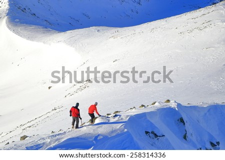 Winter mountaineers descending along snow covered ridge  - stock photo