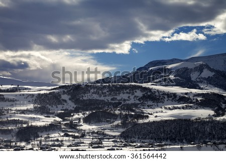 Winter mountains and village at evening. Greater Caucasus, Mount Shahdagh. Qusar rayon of Azerbaijan. - stock photo