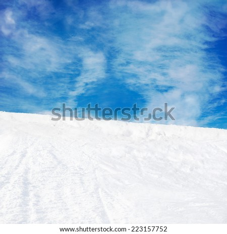 Winter mountains snow slope and blue sky background