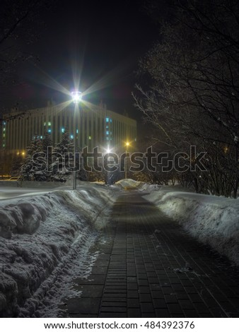 Winter night in Moscow, Russia. Brick road surrounded by snowdrifts, rays of street lamps under the dark sky. High dynamic range image from 5 exposures.